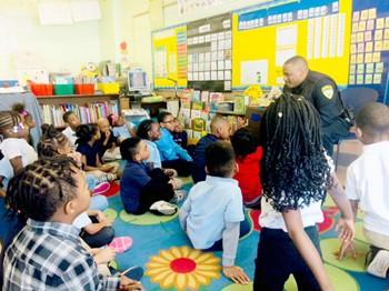Officer Thomas reading to children at John Dewey